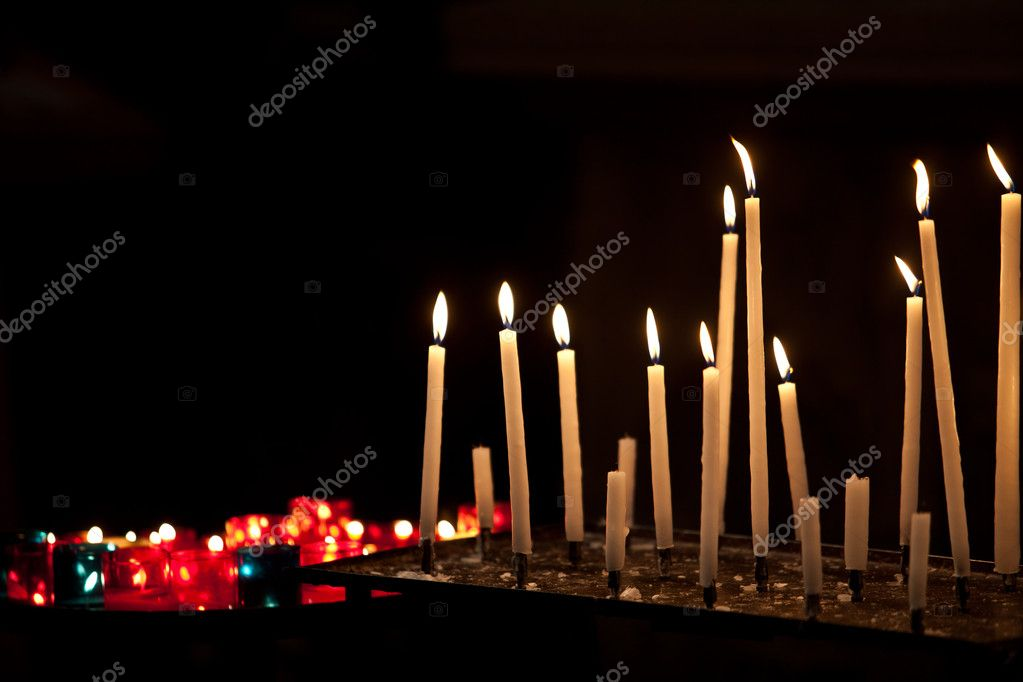 Many burning prayer candles in catholic church — Stock Photo #16254761
