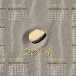 2014 english calendar with stone on sand — Stock Photo