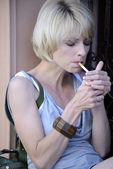 Happy woman smoking a cigarette — Stock Photo