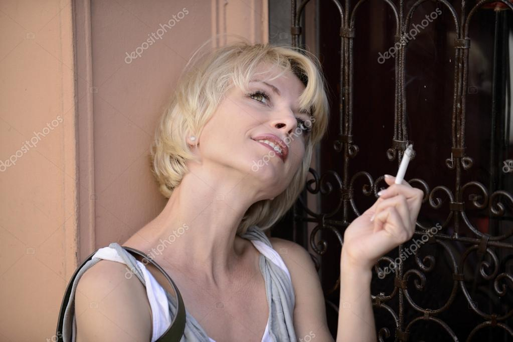 Happy woman smoking a cigarette smiling — Stock Photo #12296263