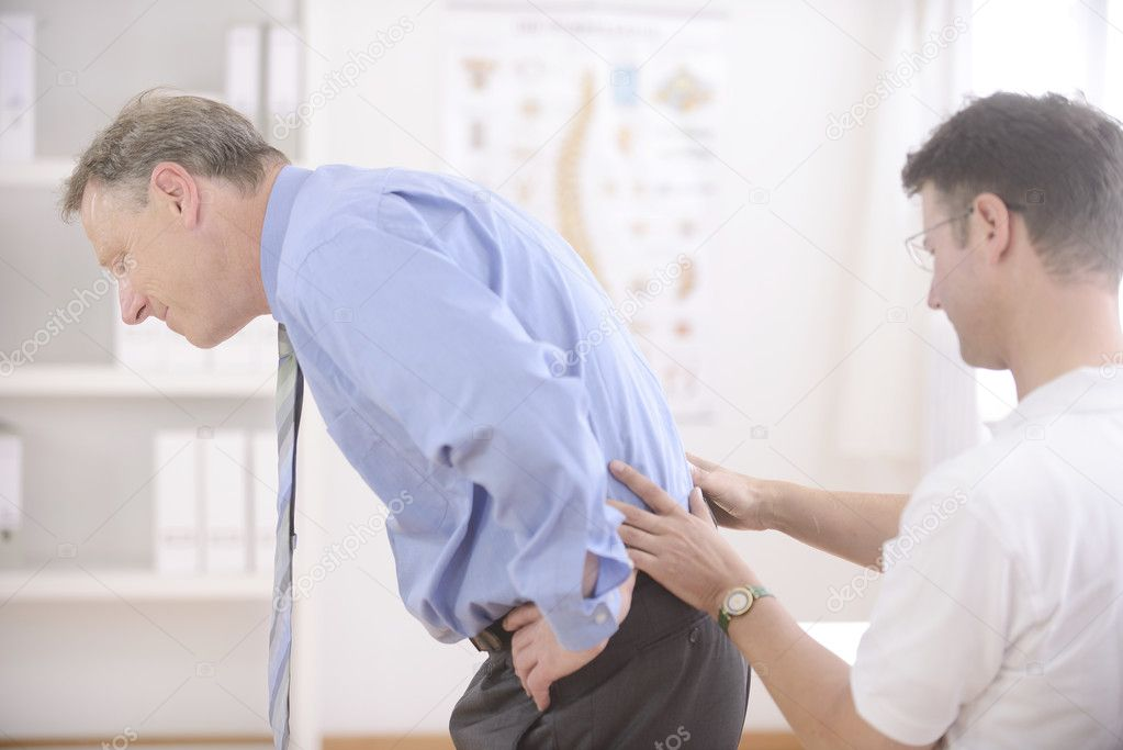 Chiropractic: Chiropractor examining senior man at office — Stock Photo #12298331