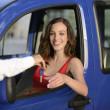 Woman receiving keys of her new car - Stock Photo