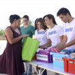 Stock Photo: Group of volunteers collecting clothing donations