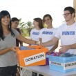 Group of volunteers collecting clothing donations - Stock Photo