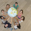 Stock Photo: Multiracial group of holding the Earth Globe