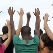 Diverse group raising hands - Stock Photo