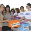 Group of volunteers collecting clothing donations — Stock Photo