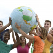 Stock Photo: Group of young holding a globe earth