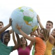 Group of young holding globe earth — Stock fotografie #15549513