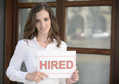 Recruitment : woman holding a hired sign — Stock Photo