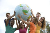 Group of young holding a globe earth — ストック写真