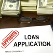 Approved loan application and dollar bills - ストック写真