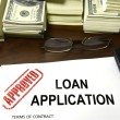 Approved loan application and dollar bills - 图库照片