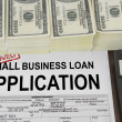 Approved small business loan application form and money - Stock Photo