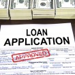 Approved loan application form and dollar bills - Stock Photo