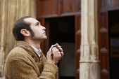 человек, молиться в церкви, холдинг четки — Стоковое фото