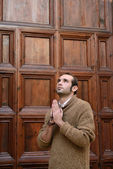Man praying in front of the church holding a cross — Stock Photo