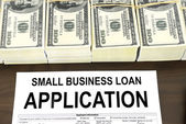 Approved small business loan application form and stacks of 100 dollar bills — Stock Photo