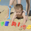 Baby on the beach with writing ferias — Photo