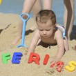 Baby on the beach with writing ferias — Stok fotoğraf
