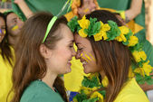 Brazilian girlfriends soccer fans kissing each other — Stock Photo