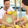 Small business owner selling organic fruits and vegetables — Stock Photo #42987035