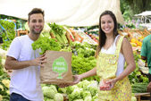 Small business owner selling organic fruits and vegetables to a woman — Stock Photo