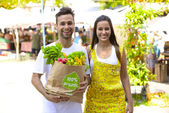 Happy couple with a shopping paper bag full of fruits and vegetabes — Stock Photo