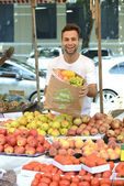 Small business owner selling organic fruits and vegetables — Stock Photo