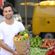 Man carrying a shopping paper bag full of fruits and vegetables — Stock fotografie