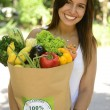 Happy woman carrying bag of organic food. — Stock Photo