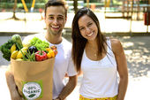 Happy couple carrying a bag of organic food — Stock Photo