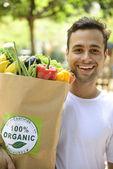 Happy man carrying bag of organic food — Stock Photo