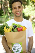Happy man carrying a bag of organic food — Stock Photo
