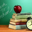School Books, Apple and Clock on Desk at School — Stock Photo #28030243