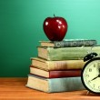 School Books, Apple and Clock on Desk at School — Stock Photo #28030883