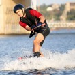 Wakeboarder surfing across a river — Stock Photo