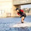Wakeboarder surfing across a river — Stockfoto