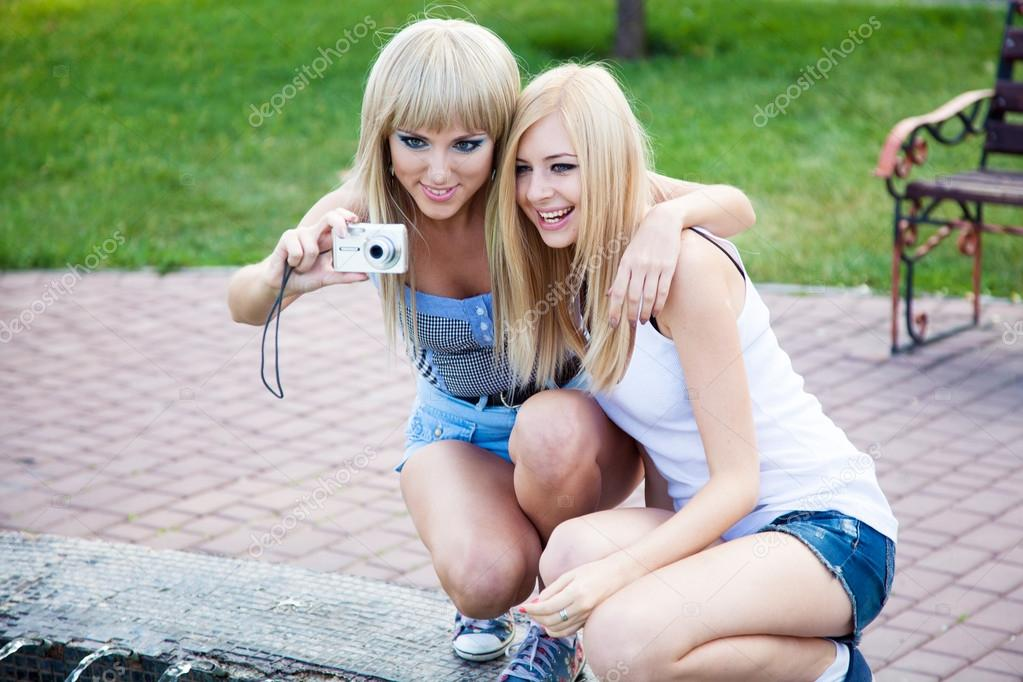 Two beautiful young girl friends with a digital photo camera — Zdjęcie stockowe #12603774