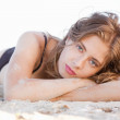 Beautiful model lying in sand — Stock Photo
