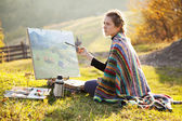 Young artist painting a landscape — Stock Photo