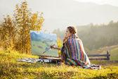 Joven artista pintando un paisaje — Foto de Stock