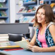 Beautiful female student in a library — Stock Photo #13977379