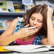 Beautiful female student in a library — Stock Photo #13977402