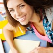 Beautiful female student in a library — Stock Photo #13977405