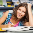Beautiful female student in a library — Stock Photo #13977407