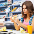 Stressed female student in a library — Stock Photo #13977415