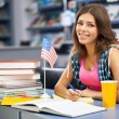 Beautiful female student in a library — Stock Photo #13977416