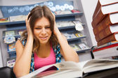 Stressed female student in a library — Stock Photo