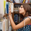 Beautiful female student in a library — Stock Photo #14030487